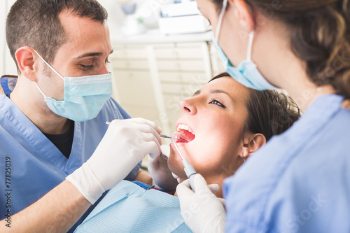 Dentist and Dental Assistant examining Patient teeth. - 77825039