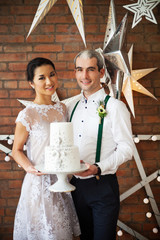 Cheerful married couple standing near the brick wall decorated w