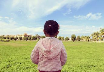 A little girl in a  garden with blue sky