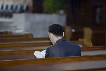 Man reading Bible in church