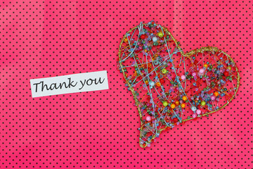 Thank you card with heart made of beads on pink background