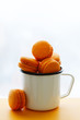 Orange macaroon cookies with backdrop on light background