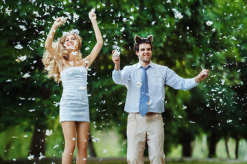 A happy young pair is throwing feathers at the green forest back