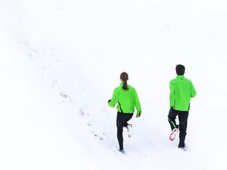 junger Mann und Frau joggen im Schnee