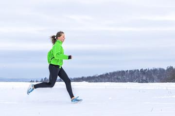 junge Frau joggt in verschneiter Winterlandschaft
