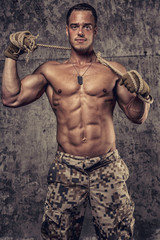 strong athletic man with naked body in military pants