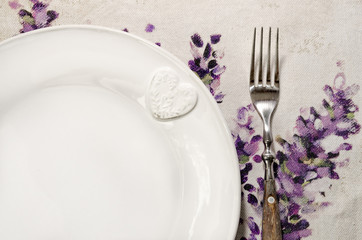 Detail of plate and fork laid on vintage wooden dining table