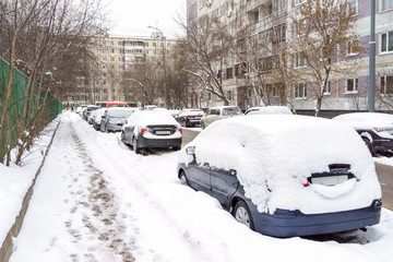 snow covered cars in parking lot