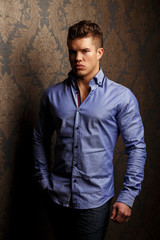 Fashion portrait of man in shirt showing his abs.