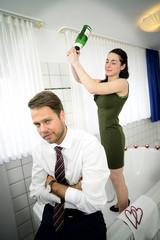Junge Braut schlägt Bräutigam mit Sektflasche