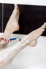 Woman shave legs in the bathroom