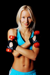 Good-shaped athletic girl stands holding dumbbell.