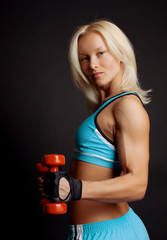 Good-shaped athletic girl stands and holds dumbbells