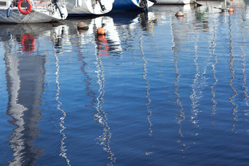Reflection of masts in the blue water