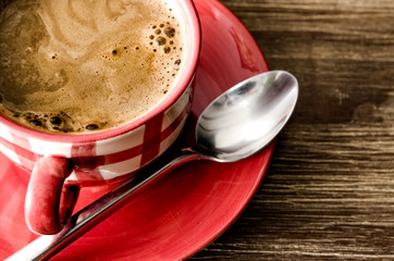 Detail of coffee in red cup on wooden vintage table