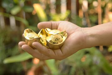 hand holding chinese gold ingots