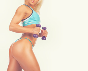Good-shaped sexy athletic girl poses and holds dumbbells