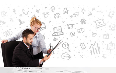 Business man and woman sitting at table with hand drawn media ic