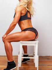 Athletic beautiful female with trained buttocks sits