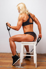 Athletic beautiful female with trained buttocks sits and trains