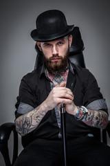 Tattoed male holding cane
