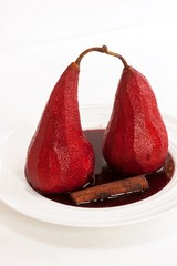 Poached pears in red wine on white background