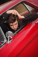 young rocker combing hair in fifties car