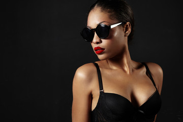woman in sunglasses and with a red lips in a dark room