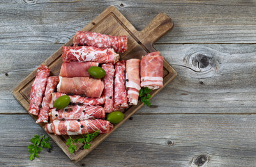 Various raw meats on rustic serving board