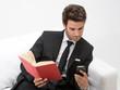 Uomo su Divano con Cellulare e Libro