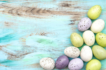Pastel colored easter eggs on wooden background