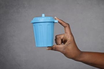 main femme noire tenant poubelle