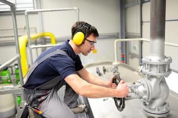 Industriearbeiter bedient Ventil // worker operating