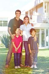 Familie mit Kindern vor Haus im Garten