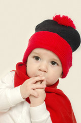 Innocent baby wearing a red hat and a muffler,looking adorable