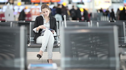 Pretty, young  businesswoman waiting for her flight on airport