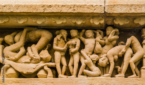 Stone carved erotic sculpture in Khajuraho temple, India - 77842406