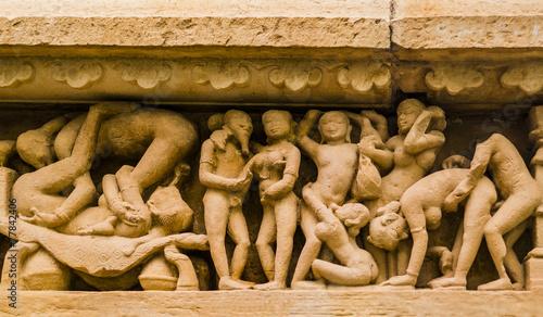 Leinwanddruck Bild Stone carved erotic sculpture in Khajuraho temple, India