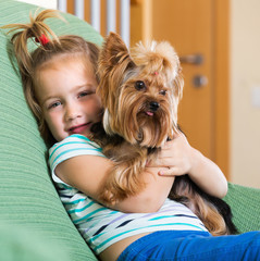 Female child playing with Yorkie