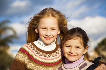 Niñas rubias sonriendo con cabello al viento