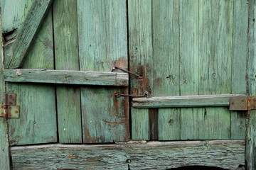 The old green shutters of window with metallic hooks