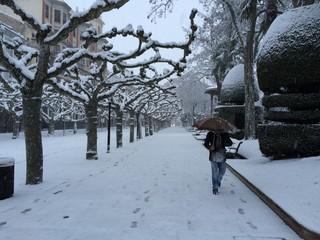 hombre pasea bajo la ciudad nevada