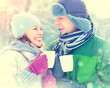 Happy winter couple drinking hot beverage outdoors