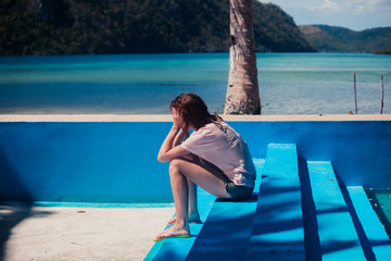 Sad woman in empty swimming pool