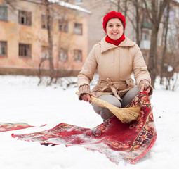 woman in red cap cleans carpet with snow