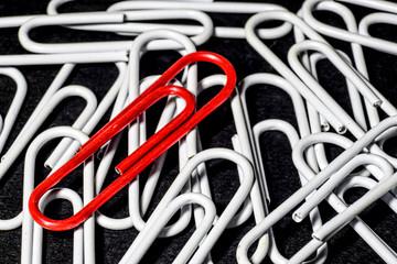 Clip rojo sobre clips blancos. Fondo negro