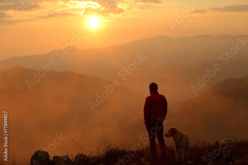 Fotobehang Alpinisme uomo e cane al tramonto