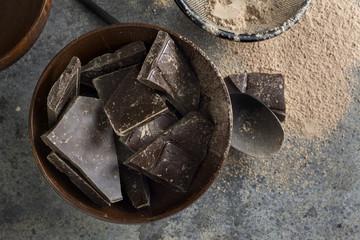 dark chocolate chunks in wooden bowl, on oak table