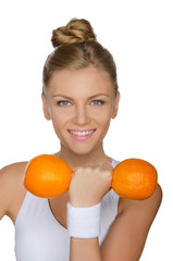 young woman with dumbbells two ripe oranges