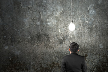 Businessman looking at brightly light bulb illuminated dark conc